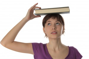 Beautiful girl  holds book on a head